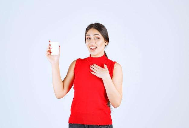Fille en chemise rouge tenant une tasse de café blanche et se pointant sur elle-même.