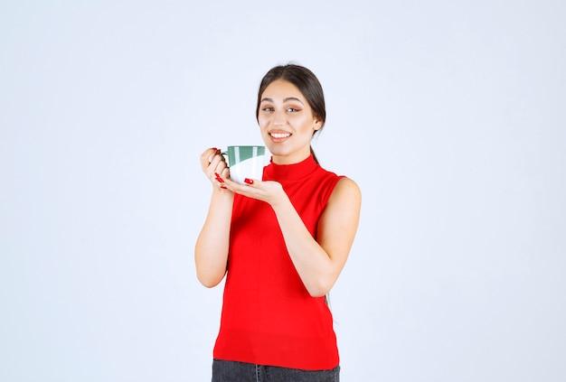 Fille en chemise rouge tenant une tasse de café.