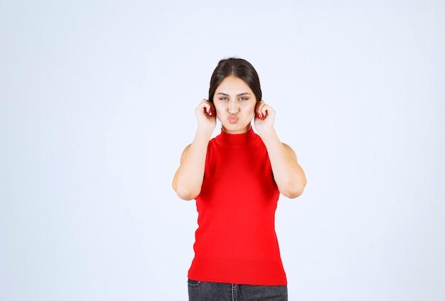 Fille en chemise rouge tirant ses oreilles en signe de malchance.