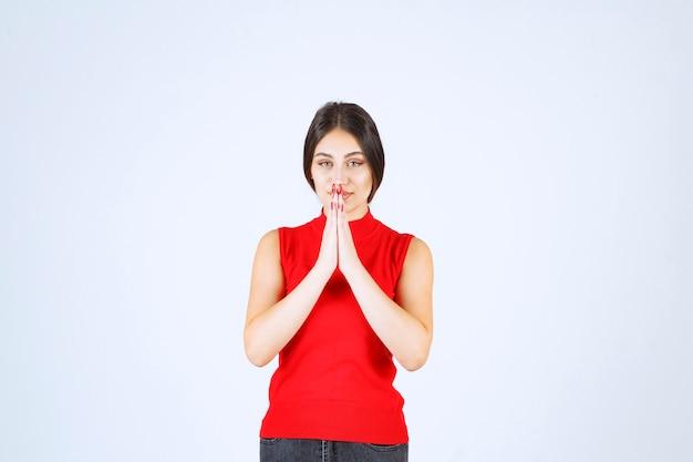 Fille en chemise rouge unissant les mains et priant.