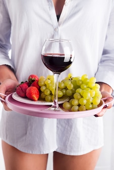 Fille en chemise tient un plateau de fruits et de vin sur fond blanc