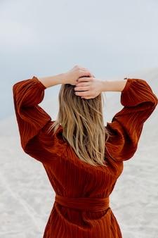 Fille en chemisier de couleur bordeaux sur un brach de sable blanc.