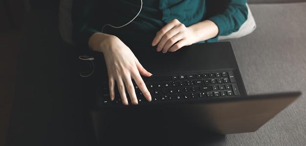 Fille en chemisier vert foncé est assise sur un canapé gris à la maison. journée de travail en tant qu'indépendant et gagner de l'argent sur internet. la femme recherche les réseaux sociaux. mains sur l'ordinateur portable noir. canapé dans l'appartement.