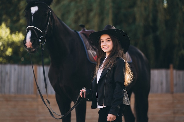 Fille avec un cheval au ranch