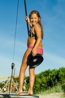 Fille à cheval sur la balançoire élastique sur l'aire de jeux du parc en journée ensoleillée d'été.