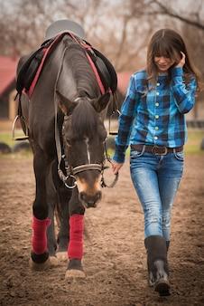 Fille avec un cheval sur ranch onn automne nuageux.