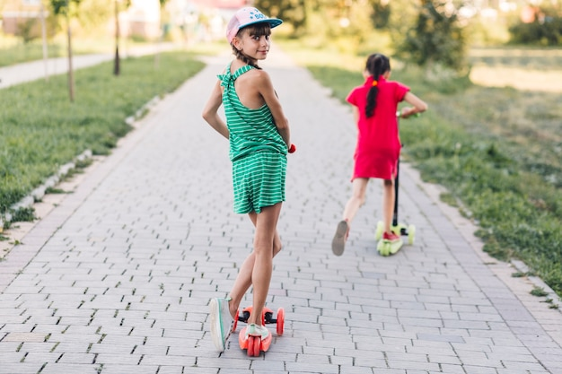 Fille à cheval sur le scooter de poussée avec son amie sur le trottoir dans le parc