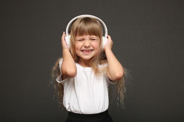 Fille de cheveux blonds yeux bleus debout et écouter de la musique.