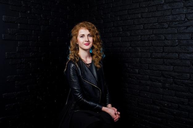Fille cheveux bouclés à la veste en cuir studio contre le mur de briques noires.
