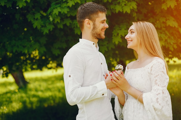 Fille avec des cheveux clairs et une robe blanche marche dans une forêt ensoleillée avec son petit ami