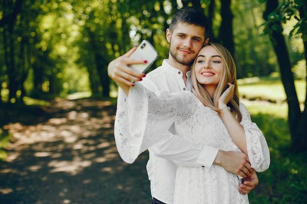 Fille avec des cheveux clairs et une robe blanche prend une photo dans une forêt ensoleillée avec son petit ami