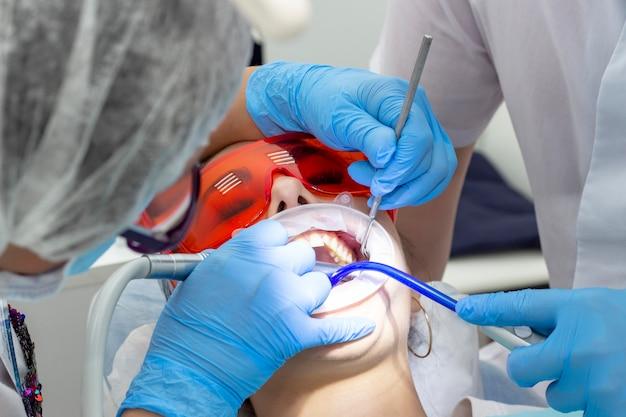 Fille chez le dentiste. traitement de la dent carieuse.