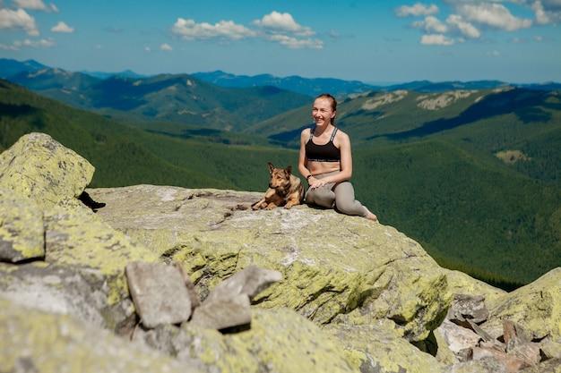 Fille avec un chien au sommet d'une montagne en regardant un beau paysage avec les bras grands ouverts