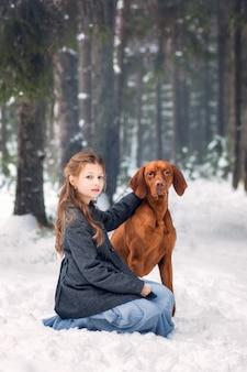 Fille et chien brun dans la nature en hiver