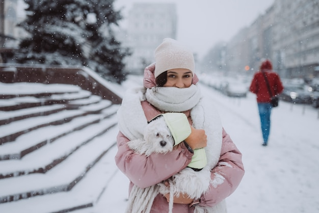 Fille avec un chien dans ses bras sur une rue de la ville la neige tombe