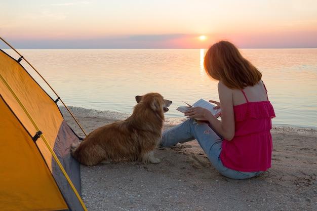 Fille avec un chien dans une tente sur la plage à l'aube