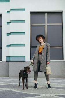 Fille avec un chien debout dans le contexte d'un mur avec des fenêtres et posant à la caméra