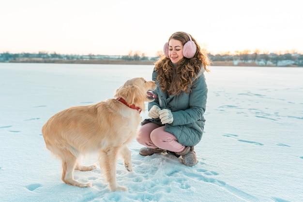Fille et chien gros golden retriever. paysage blanc d'hiver.