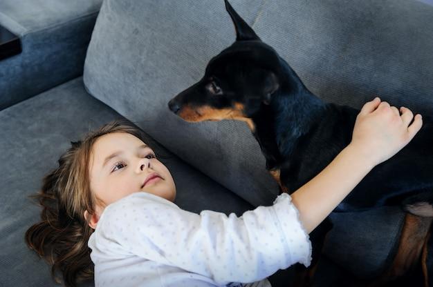La fille avec le chien joue sur le canapé.
