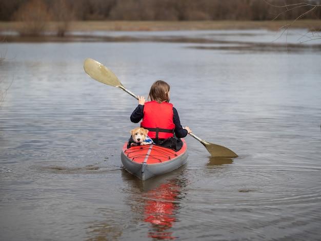 Une fille avec un chien sur un kayak rouge nage au loin.