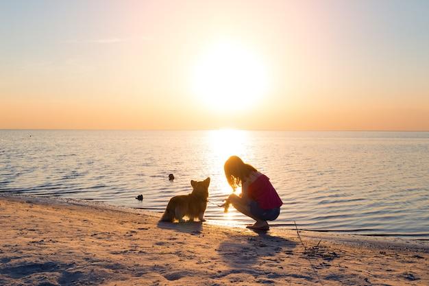 Fille avec un chien sur la plage