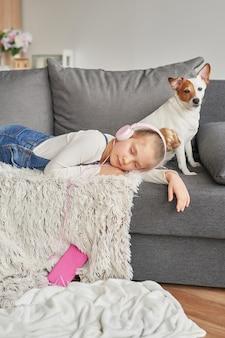 Fille et chien portant sur un canapé dans les écouteurs, écouter de la musique avec son smartphone