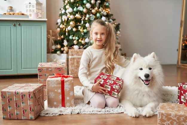 Fille avec un chien près de l'arbre de noël sur la scène de noël