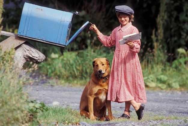 Fille avec chien récupérant des lettres de la boîte aux lettres