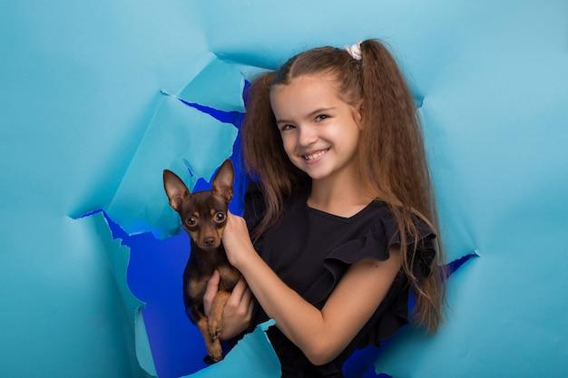 Fille avec un chien regarde dans un trou dans du papier bleu