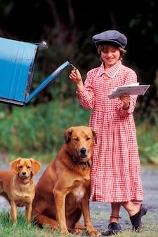 Fille avec des chiens récupérant des lettres d'une boîte aux lettres