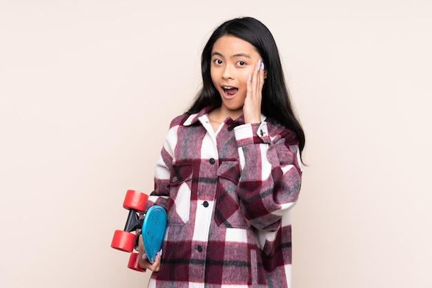 Fille chinoise adolescente isolée sur beige avec un patin et faisant un geste surprise
