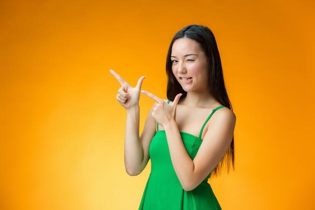 La fille chinoise heureuse sur mur jaune