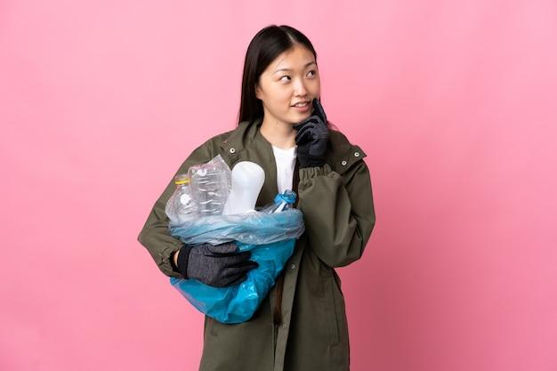 Fille chinoise tenant un sac plein de bouteilles en plastique à recycler isolé