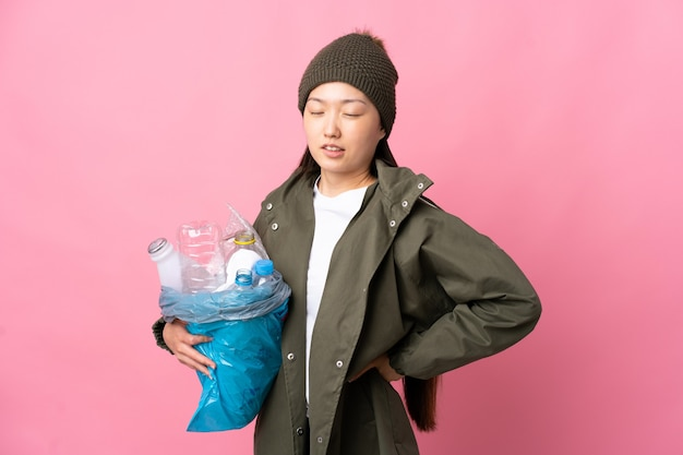 Fille chinoise tenant un sac plein de bouteilles en plastique à recycler sur un mur rose isolé souffrant de maux de dos pour avoir fait un effort