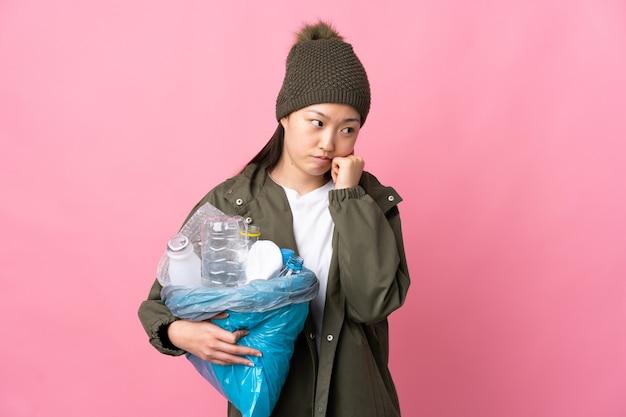 Fille chinoise tenant un sac plein de bouteilles en plastique à recycler sur rose isolé avec une expression fatiguée et ennuyée