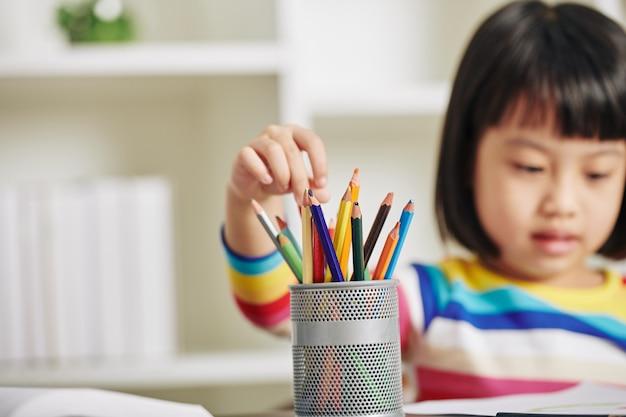 Fille choisissant un crayon pour dessiner