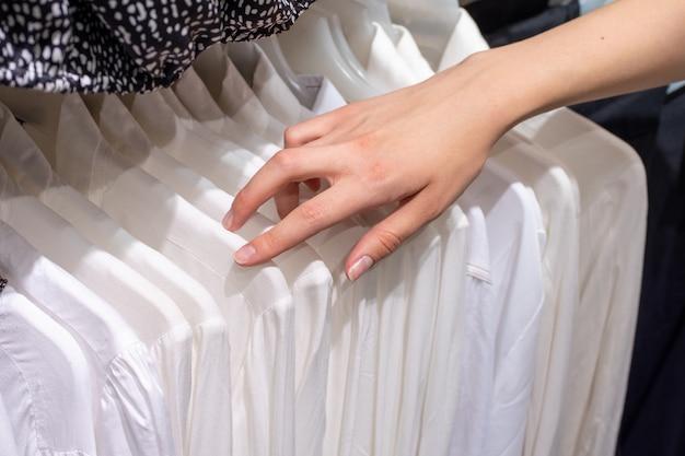 Fille choisit une chemise blanche dans le magasin. sélection de nouveaux vêtements gros plan des mains.