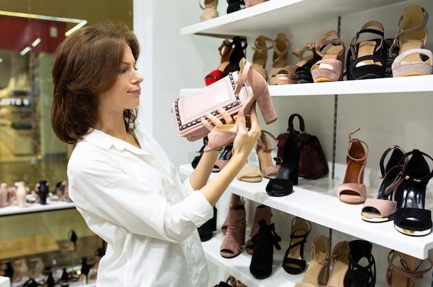 Une fille choisit des talons hauts dans un magasin de chaussures.