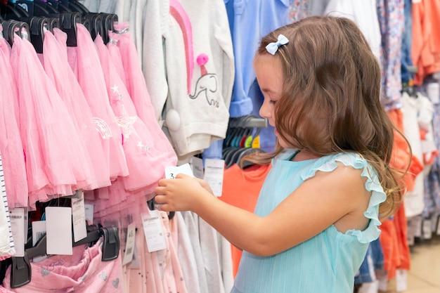 Fille choisit des vêtements dans un magasin de vêtements