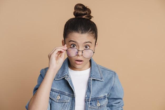Une fille choquée avec ses cheveux enlevés regarde à travers ses lunettes avec surprise. petite fille sur fond marron