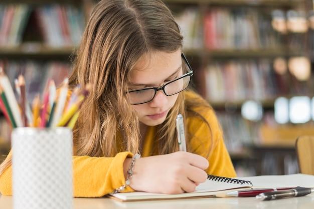 Fille ciblée à faire ses devoirs dans la bibliothèque