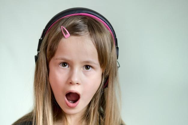 Fille cild très souriante, écouter de la musique dans de gros écouteurs roses.