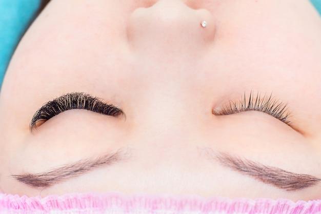 La fille avec les cils augmentés sur un œil. comparaison de l'augmentation des cils avec d'habitude