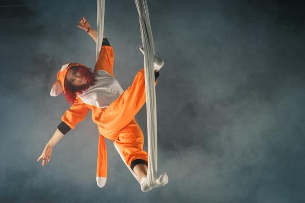 Fille de cirque aux cheveux roux faisant un tour de fanny sur de la soie aérienne en pyjama de renard orange.
