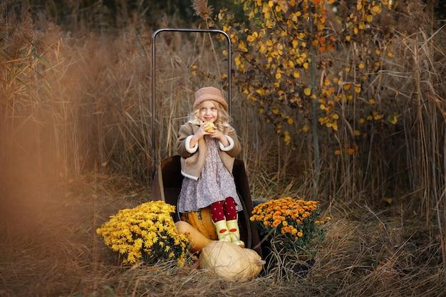 Fille avec des citrouilles en automne sur une promenade