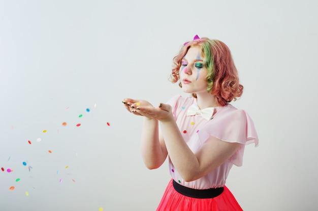 Fille de clown souffle des confettis des mains