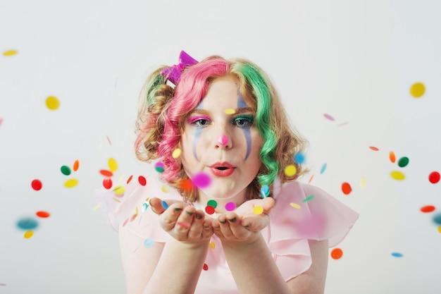 Fille clown souffle des confettis des mains