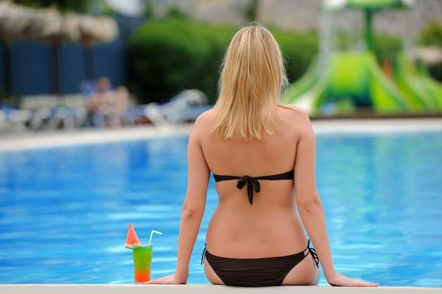 Fille avec un cocktail au bord de la piscine
