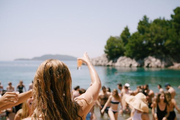 Fille avec un cocktail à la main regarde les gens qui sortent de la vue arrière de la mer