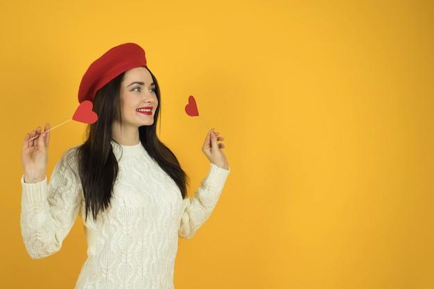Fille avec coeur sur un mur jaune uni monochrome